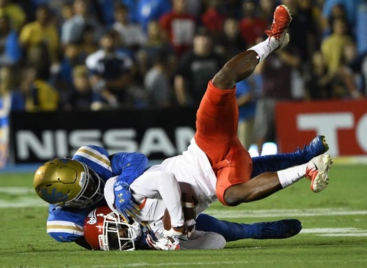 Sep 15, 2018; Pasadena, CA, USA; Fresno State Bulldogs wide receiver Jamire Jordan (1) is upended by UCLA Bruins defensive back Darnay Holmes (1) during the first quarter at Rose Bowl. Mandatory Credit: Robert Hanashiro-USA TODAY Sports