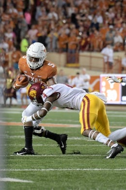 Sep 15, 2018; Austin, TX, USA; Texas Longhorns running back Tre Watson (5) rushes against Southern California Trojans cornerback Olaijah Griffin (4) during the second half at Darrell K Royal-Texas Memorial Stadium. Mandatory Credit: Kirby Lee-USA TODAY Sports