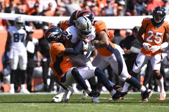 Sep 16, 2018; Denver, CO, USA; Denver Broncos defensive back Justin Simmons (31) and defensive end Shelby Harris (96) and linebacker Shane Ray (56) tackle Oakland Raiders running back Marshawn Lynch (24) in the first quarter at Broncos Stadium at Mile High. Mandatory Credit: Ron Chenoy-USA TODAY Sports