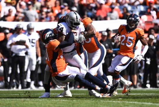 Sep 16, 2018; Denver, CO, USA; Oakland Raiders running back Marshawn Lynch (24) is tackled by Denver Broncos defensive back Justin Simmons (31) and linebacker Shane Ray (56) in the first quarter at Broncos Stadium at Mile High. Mandatory Credit: Ron Chenoy-USA TODAY Sports