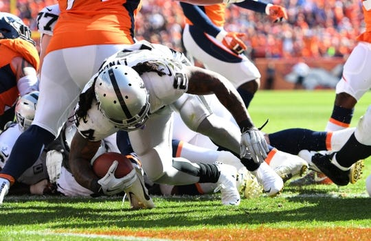 Sep 16, 2018; Denver, CO, USA; Oakland Raiders running back Marshawn Lynch (24) scores a touchdown in the second quarter against the Denver Broncos at Broncos Stadium at Mile High. Mandatory Credit: Ron Chenoy-USA TODAY Sports