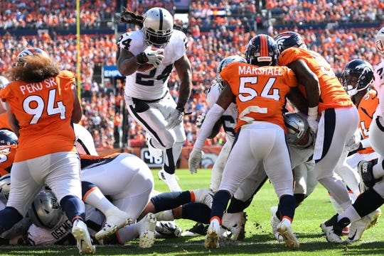 Sep 16, 2018; Denver, CO, USA; Oakland Raiders running back Marshawn Lynch (24) leaps for a touchdown carry in the second quarter against the Denver Broncos at Broncos Stadium at Mile High. Mandatory Credit: Ron Chenoy-USA TODAY Sports