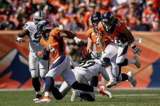 Sep 16, 2018; Denver, CO, USA; Denver Broncos wide receiver Courtland Sutton (14) defends as running back Phillip Lindsay (30) runs through the tackle of Oakland Raiders safety Reggie Nelson (27) with defensive tackle Clinton McDonald (97) and center Matt Paradis (61) behind the play in the second quarter at Broncos Stadium at Mile High. Mandatory Credit: Isaiah J. Downing-USA TODAY Sports