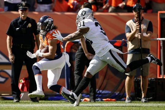 Sep 16, 2018; Denver, CO, USA; Oakland Raiders safety Marcus Gilchrist (31) pushes Denver Broncos running back Phillip Lindsay (30) out of bounds in the second quarter at Broncos Stadium at Mile High. Mandatory Credit: Isaiah J. Downing-USA TODAY Sports