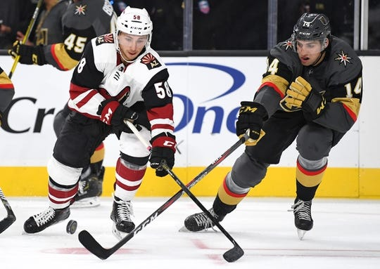 Sep 16, 2018; Las Vegas, NV, USA; Vegas Golden Knights defenseman Nicolas Hague (14) tips the puck away from Arizona Coyotes left wing Michael Bunting (58) during the first period at T-Mobile Arena. Mandatory Credit: Stephen R. Sylvanie-USA TODAY Sports