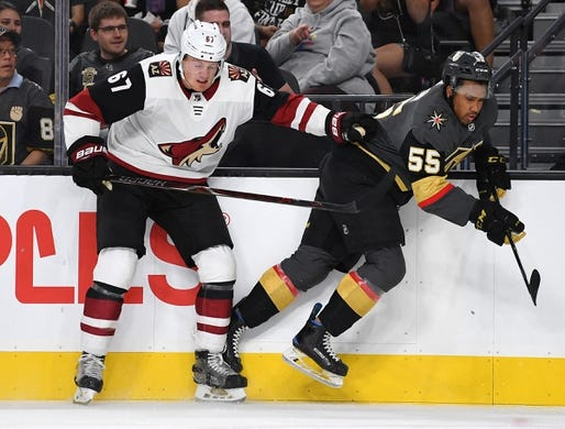Sep 16, 2018; Las Vegas, NV, USA; Arizona Coyotes left wing Lawson Crouse (67) pushes Vegas Golden Knights right wing Keegan Kolesar (55) off the puck during the first period at T-Mobile Arena. Mandatory Credit: Stephen R. Sylvanie-USA TODAY Sports