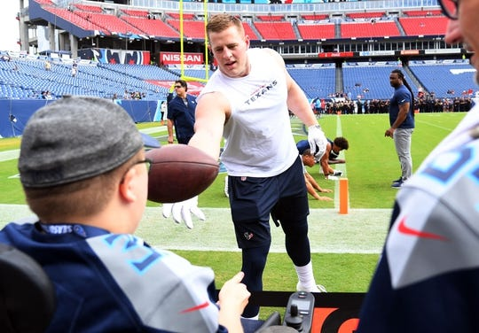 Sep 16, 2018; Nashville, TN, USA; Houston Texans defensive end J.J. Watt (99) tosses a ball to a Tennessee Titans fan before the game at Nissan Stadium. Mandatory Credit: Christopher Hanewinckel-USA TODAY Sports