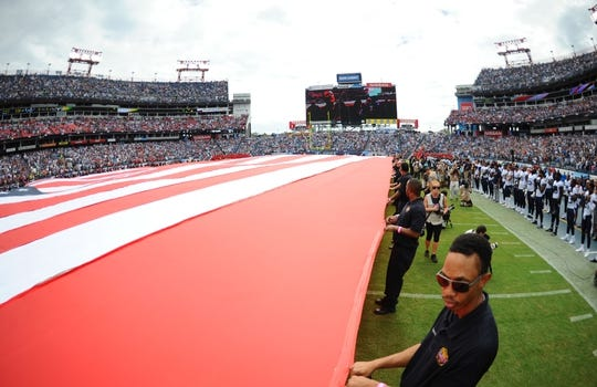 Sep 16, 2018; Nashville, TN, USA; Local first responders hold a large flag during the national anthem before the game between the Tennessee Titans and the Houston Texans at Nissan Stadium. Mandatory Credit: Christopher Hanewinckel-USA TODAY Sports