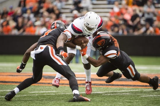 Sep 22, 2018; Corvallis, OR, USA; Oregon State Beavers linebacker Doug Taumoelau (42) and linebacker Kee Whetzel (7) tackle Arizona Wildcats quarterback Khalil Tate (14) during the first half at Reser Stadium. Mandatory Credit: Troy Wayrynen-USA TODAY Sports