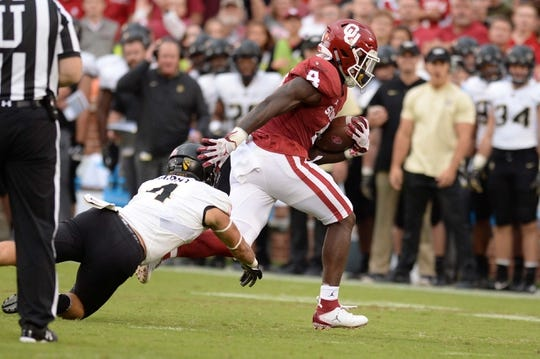 Sep 22, 2018; Norman, OK, USA; Oklahoma Sooners running back Trey Sermon (4) is tripped by Army Black Knights defensive back Max Regan (4) during the first quarter at Gaylord Family - Oklahoma Memorial Stadium. Mandatory Credit: Mark D. Smith-USA TODAY Sports