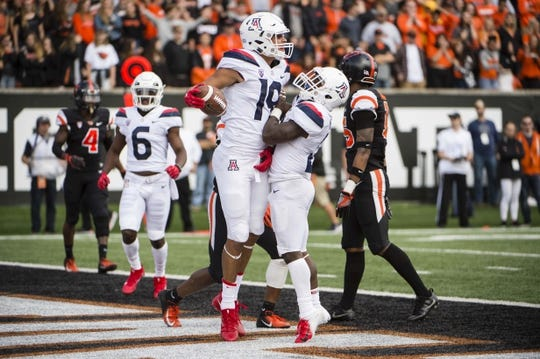 Sep 22, 2018; Corvallis, OR, USA; Arizona Wildcats wide receiver Shawn Poindexter (19) celebrates with running back J.J. Taylor (21) after scoring a touchdown during the second half against the Oregon State Beavers at Reser Stadium. The Arizona Wildcats won 35-14. Mandatory Credit: Troy Wayrynen-USA TODAY Sports