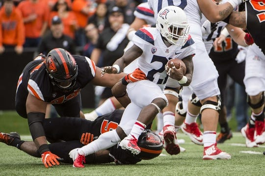 Sep 22, 2018; Corvallis, OR, USA; Arizona Wildcats running back J.J. Taylor (21) breaks away from Oregon State Beavers defenders during the first half at Reser Stadium. The Arizona Wildcats won 35-14. Mandatory Credit: Troy Wayrynen-USA TODAY Sports