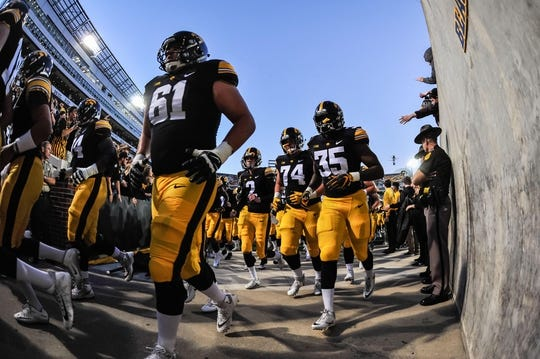 Sep 22, 2018; Iowa City, IA, USA; Iowa Hawkeyes offensive lineman Cole Banwart (61) and linebacker Barrington Wade (35) head off the field before the game between the Hawkeyes and the Wisconsin Badgers at Kinnick Stadium. Mandatory Credit: Jeffrey Becker-USA TODAY Sports