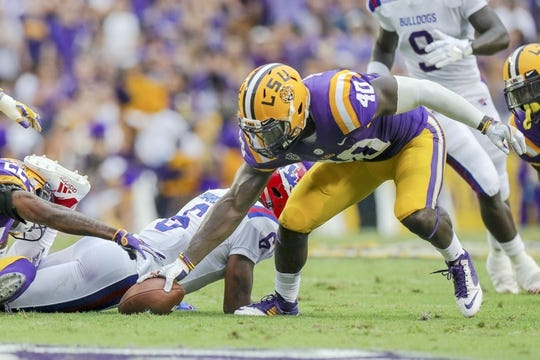 Sep 22, 2018; Baton Rouge, LA, USA; LSU Tigers linebacker Devin White (40) picks up a fumble against Louisiana Tech Bulldogs at Tiger Stadium. Mandatory Credit: Stephen Lew-USA TODAY Sports