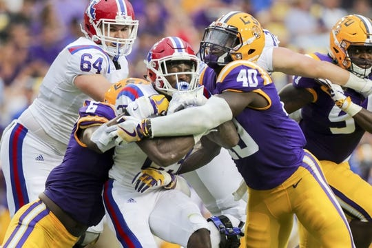 Sep 22, 2018; Baton Rouge, LA, USA; Louisiana Tech Bulldogs running back Jaqwis Dancy (23) is tackled by LSU Tigers linebacker Devin White (40) in the first quarter at Tiger Stadium. Mandatory Credit: Stephen Lew-USA TODAY Sports