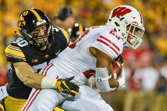 Sep 22, 2018; Iowa City, IA, USA; Wisconsin Badgers running back Jonathan Taylor (23) runs the ball as Iowa Hawkeyes defensive back Jake Gervase (30) makes the tackle during the first quarter at Kinnick Stadium. Mandatory Credit: Jeffrey Becker-USA TODAY Sports