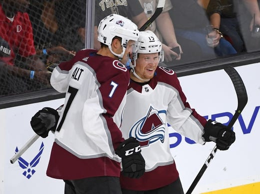 Sep 24, 2018; Las Vegas, NV, USA; Colorado Avalanche center Sheldon Dries (15) celebrates with Colorado Avalanche defenseman Mark Alt (7) after scoring a second period goal against the Vegas Golden Knights at T-Mobile Arena. Mandatory Credit: Stephen R. Sylvanie-USA TODAY Sports