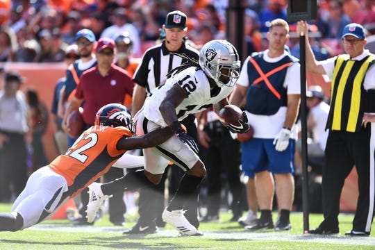 Sep 16, 2018; Denver, CO, USA; Denver Broncos defensive back Tramaine Brock (22) attempts to tackle Oakland Raiders wide receiver Martavis Bryant (12) in the second quarter at Broncos Stadium at Mile High. Mandatory Credit: Ron Chenoy-USA TODAY Sports