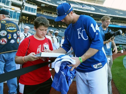 Sep 27, 2018; Kansas City, MO, USA; Kansas City Royals right fielder Brett Phillips (14) signs autographs for a fan before the game against the Cleveland Indians at Kauffman Stadium. Mandatory Credit: Jay Biggerstaff-USA TODAY Sports