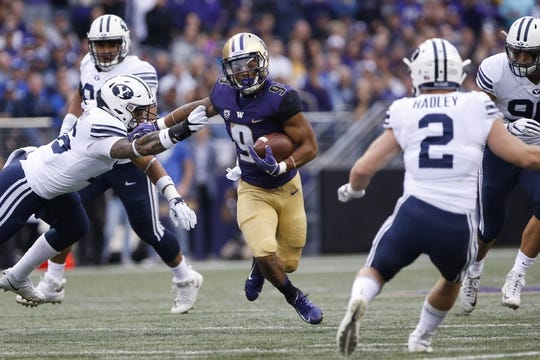 Sep 29, 2018; Seattle, WA, USA; Washington Huskies running back Myles Gaskin (9) pushes past Brigham Young Cougars linebacker Sione Takitaki (16) during the first quarter at Husky Stadium. Mandatory Credit: Jennifer Buchanan-USA TODAY Sports