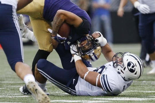 Sep 29, 2018; Seattle, WA, USA; Washington Huskies wide receiver Aaron Fuller (2) is pulled down by his helmet by Brigham Young Cougars linebacker Butch Pau'u (38) during the first quarter at Husky Stadium. Mandatory Credit: Jennifer Buchanan-USA TODAY Sports