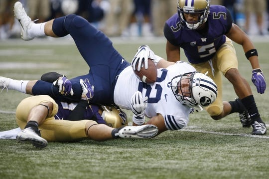 Sep 29, 2018; Seattle, WA, USA; Washington Huskies defensive back Taylor Rapp (left) and defensive back Myles Bryant (right) tackle Brigham Young Cougars running back Squally Canada (22) during the first quarter at Husky Stadium. Mandatory Credit: Jennifer Buchanan-USA TODAY Sports