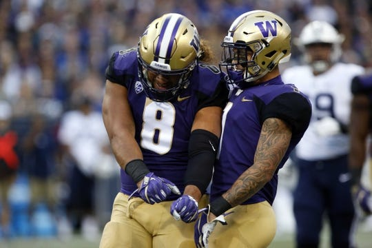 Sep 29, 2018; Seattle, WA, USA; Washington Huskies linebacker Benning Potoa'e (8) celebrates a tackle for loose with defensive back Byron Murphy (1) against the Brigham Young Cougars during the first quarter at Husky Stadium. Mandatory Credit: Jennifer Buchanan-USA TODAY Sports
