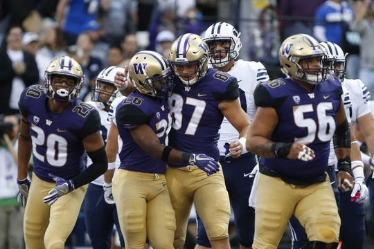 Sep 29, 2018; Seattle, WA, USA; Washington Huskies running back Salvon Ahmed (26) is congratulated by tight end Cade Otton (87) after Ahmed scored on a five-yard touchdown run against the Brigham Young Cougars during the first quarter at Husky Stadium. Mandatory Credit: Jennifer Buchanan-USA TODAY Sports
