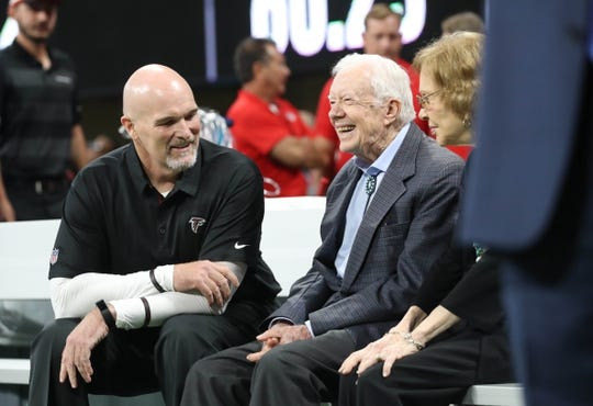 Sep 30, 2018; Atlanta, GA, USA; Atlanta Falcons head coach Dan Quinn (left) talks with former President Jimmy Carter (middle) and his wife Rosalyn before a game between the Falcons and the Cincinnati Bengals at Mercedes-Benz Stadium. Mandatory Credit: Jason Getz-USA TODAY Sports