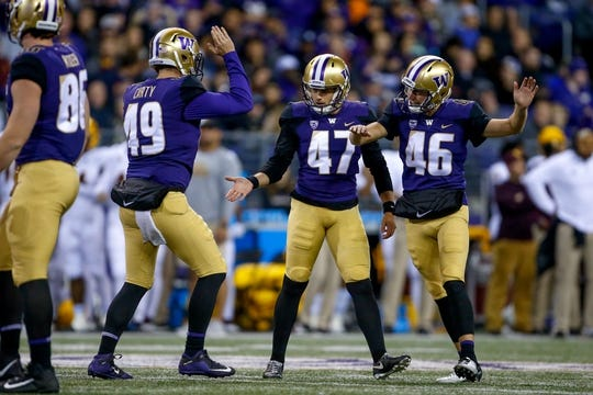 Sep 22, 2018; Seattle, WA, USA; Washington Huskies long snapper A.J. Carty (49) slaps hands with place kicker Peyton Henry (47) and holder Race Porter (46) during the third quarter against the Arizona State Sun Devils at Husky Stadium. Mandatory Credit: Jennifer Buchanan-USA TODAY Sports