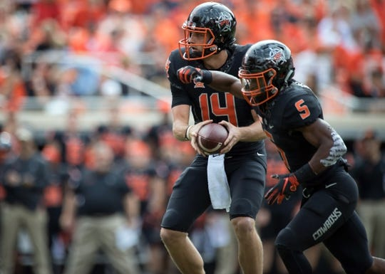 Oct 6, 2018; Stillwater, OK, USA; Oklahoma State Cowboys quarterback Taylor Cornelius (14) hands off to Oklahoma State Cowboys running back Justice Hill (5) against the Iowa State Cyclones during the first quarter at Boone Pickens Stadium. Mandatory Credit: Rob Ferguson-USA TODAY Sports