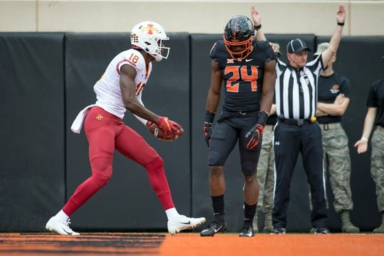Oct 6, 2018; Stillwater, OK, USA; Iowa State Cyclones wide receiver Hakeem Butler (18) scores a touchdown as Oklahoma State Cowboys safety Jarrick Bernard (24) reacts during the first quarterat Boone Pickens Stadium. Mandatory Credit: Rob Ferguson-USA TODAY Sports
