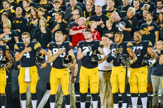 Sep 22, 2018; Iowa City, IA, USA; Iowa Hawkeyes quarterback Nate Stanley (4) and tight end Noah Fant (right) and teammates stand for the national anthem before the game against the Wisconsin Badgers at Kinnick Stadium. Mandatory Credit: Jeffrey Becker-USA TODAY Sports