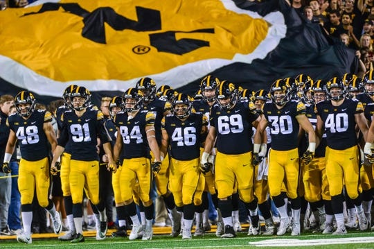 Sep 22, 2018; Iowa City, IA, USA; The Iowa Hawkeyes swarm enter the field before the game against the Wisconsin Badgers at Kinnick Stadium. Mandatory Credit: Jeffrey Becker-USA TODAY Sports