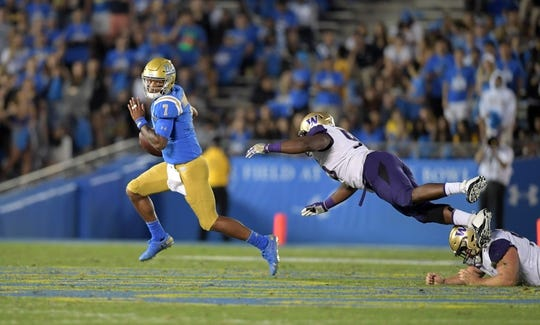 Oct 6, 2018; Pasadena, CA, USA; UCLA Bruins quarterback Dorian Thompson-Robinson (7) is pursued by Washington Huskies defensive lineman Levi Onwuzurike (95) in the third quarter at Rose Bowl. Washington defeated UCLA 31-24. Mandatory Credit: Kirby Lee-USA TODAY Sports