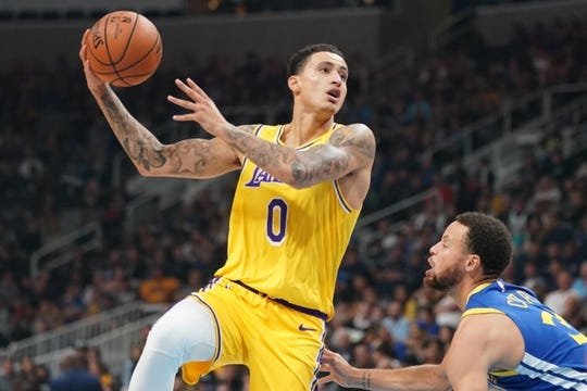 October 12, 2018; San Jose, CA, USA; Los Angeles Lakers forward Kyle Kuzma (0) shoots the basketball against Golden State Warriors guard Stephen Curry (30) during the first quarter at SAP Center. Mandatory Credit: Kyle Terada-USA TODAY Sports