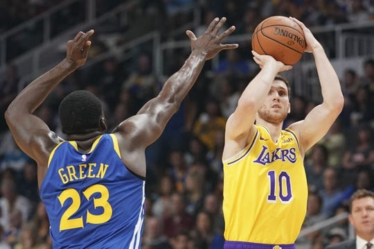 October 12, 2018; San Jose, CA, USA; Los Angeles Lakers forward Sviatoslav Mykhailiuk (10) shoots the basketball against Golden State Warriors forward Draymond Green (23) during the first quarter at SAP Center. Mandatory Credit: Kyle Terada-USA TODAY Sports