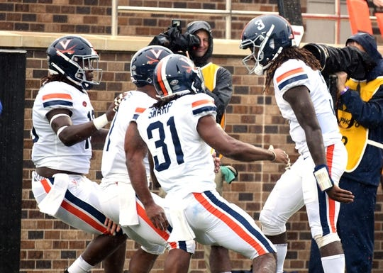 Oct 20, 2018; Durham, NC, USA; Virginia Cavaliers quarterback Bryce Perkins (3) is congratulated by teammates after scoring a touchdown during the first half against the Duke Blue Devils at Wallace Wade Stadium. Mandatory Credit: Rob Kinnan-USA TODAY Sports