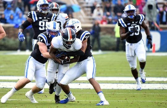 Oct 20, 2018; Durham, NC, USA; Virginia Cavaliers receiver Hasise Dubois (8) fights for a first down as Duke Blue Devils linebacker Ben Humphreys (34) and safety Brandon Feamster (30) defend during the first half at Wallace Wade Stadium. Mandatory Credit: Rob Kinnan-USA TODAY Sports
