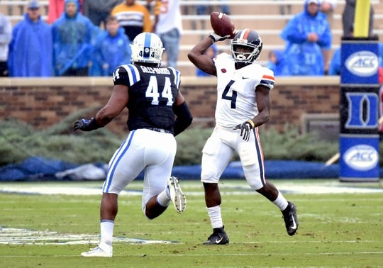 Oct 20, 2018; Durham, NC, USA; Virginia Cavaliers running back Olamide Zaccheus (4) throws a pass in front of Duke Blue Devils linebacker Joe Giles-Harris (44) during the first half at Wallace Wade Stadium. Mandatory Credit: Rob Kinnan-USA TODAY Sports