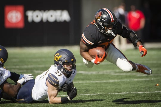 Oct 20, 2018; Corvallis, OR, USA; California Golden Bears safety Ashtyn Davis (27) trips up Oregon State Beavers running back Artavis Pierce (21) during the first half at Reser Stadium. Mandatory Credit: Troy Wayrynen-USA TODAY Sports