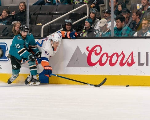 Oct 20, 2018; San Jose, CA, USA; San Jose Sharks defenseman Erik Karlsson (65) and New York Islanders left wing Anders Lee (27) battle for the puck during the first period at SAP Center at San Jose. Mandatory Credit: Neville E. Guard-USA TODAY Sports