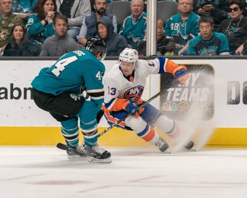 Oct 20, 2018; San Jose, CA, USA; New York Islanders center Mathew Barzal (13) and San Jose Sharks defenseman Marc-Edouard Vlasic (44) fight for the puck during the first period at SAP Center at San Jose. Mandatory Credit: Neville E. Guard-USA TODAY Sports