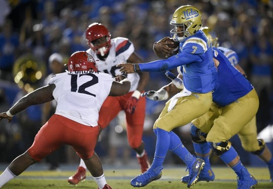 Oct 20, 2018; Pasadena, CA, USA; UCLA Bruins quarterback Dorian Thompson-Robinson (7) runs the ball while under pressure by Arizona Wildcats defensive end JB Brown (12) during the first half at Rose Bowl. Mandatory Credit: Kelvin Kuo-USA TODAY Sports