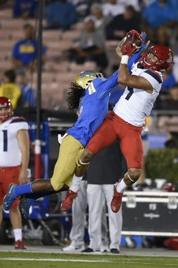 Oct 20, 2018; Pasadena, CA, USA; Arizona Wildcats wide receiver Shawn Poindexter (19) makes a catch defended by UCLA Bruins defensive back Elijah Gates (9) during the first half at Rose Bowl. Mandatory Credit: Kelvin Kuo-USA TODAY Sports