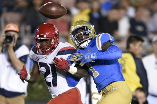Oct 20, 2018; Pasadena, CA, USA; UCLA Bruins defensive back Darnay Holmes (1) knocks the ball away from Arizona Wildcats running back J.J. Taylor (21) for a fumble during the first half at Rose Bowl. Mandatory Credit: Kelvin Kuo-USA TODAY Sports