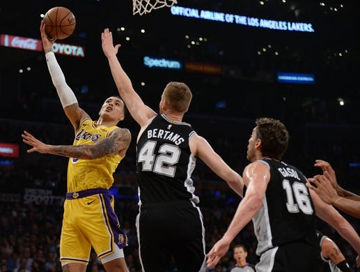 October 22, 2018; Los Angeles, CA, USA; Los Angeles Lakers forward Kyle Kuzma (0) moves to the basket against San Antonio Spurs forward Davis Bertans (42) and center Pau Gasol (16) during the first half at Staples Center. Mandatory Credit: Gary A. Vasquez-USA TODAY Sports