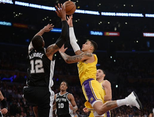 October 22, 2018; Los Angeles, CA, USA; Los Angeles Lakers forward Kyle Kuzma (0) moves to the basket against the defense of San Antonio Spurs forward LaMarcus Aldridge (12) during the first half at Staples Center. Mandatory Credit: Gary A. Vasquez-USA TODAY Sports