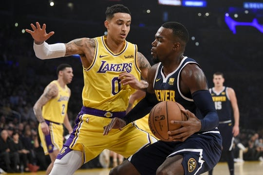 Oct 25, 2018; Los Angeles, CA, USA; Denver Nuggets forward Paul Millsap (4) handles the ball while Los Angeles Lakers forward Kyle Kuzma (0) defends during the first half at Staples Center. Mandatory Credit: Kelvin Kuo-USA TODAY Sports
