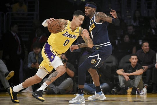 Oct 25, 2018; Los Angeles, CA, USA; Los Angeles Lakers forward Kyle Kuzma (0) drives to the basket as Denver Nuggets forward Torrey Craig (3) defends during the first half at Staples Center. Mandatory Credit: Kelvin Kuo-USA TODAY Sports